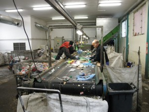 Workers sort an incoming stream of various plastics, mixed with some pieces of un-recyclable litter