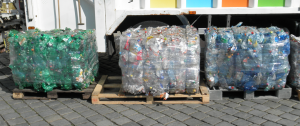 Bales of crushed PET bottles sorted according to color: green, transparent, and blue